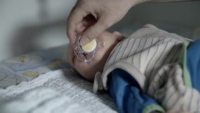 Baby crying with pacifier. Baby boy crying with pacifier on nursing table stock video footage