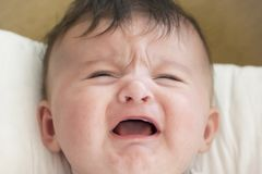 Baby is crying. Baby screaming because her stomach hurts. Screaming baby royalty free stock images