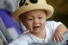 Baby crying in stroller. Baby sitting in stroller crying stock images