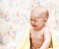 Baby crying in a yellow towel Stock Image