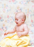 Baby crying in a yellow towel Stock Images
