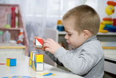 Baby and Cubes. Baby plays in the Cubes at a table in a kindergarten Stock Photography