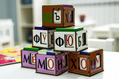 Baby playing cubes. Baby cubes from tree for study of the alphabet to rest upon table Royalty Free Stock Photos
