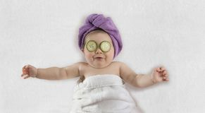 Baby with cucumber eye treatment stock photos