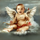 Baby cupid with angel wings. Sitting on a cloud stock image
