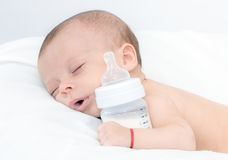 Baby curled up sleeping on a blanket with feeding bottle stock images