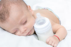 Baby curled up sleeping on a blanket with feeding bottle. Newborn baby curled up sleeping on a blanket with feeding bottle Royalty Free Stock Photo