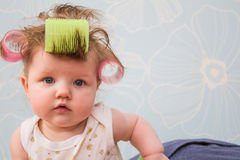 The baby with curlers in her hair. Stock Image