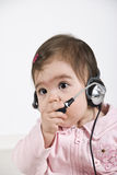 Baby customer service. Portrait of attentive baby girl customer service  with headset holding hand on microphone and  looking away.Check also Children Stock Photos