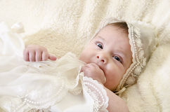 Baby and cute cap. Portrait of baby biting hands with ceremonial clothes Royalty Free Stock Images