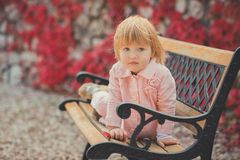 Baby cute girl with blond hair and pink apple cheek enjoying spring autumn time holiday posing in beautiful garden full of flowers stock photography