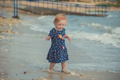 Baby cute girl with blond hair and pink apple cheek enjoying summer time holiday posing in beautiful beach full of sand wearing st. Ylish dress Royalty Free Stock Images