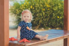 Baby cute girl with blond hair and pink apple cheek enjoying summer time holiday posing in beautiful beach full of sand wearing st. Ylish dress Royalty Free Stock Photos