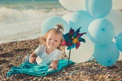 Baby cute girl with blond hair and pink apple cheek enjoying summer time holiday posing on sand beach sea side with blue white bal. Loons wearing casual kids Stock Photo