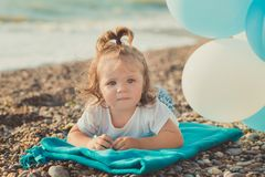 Baby cute girl with blond hair and pink apple cheek enjoying summer time holiday posing on sand beach sea side with blue white bal. Loons wearing casual kids Royalty Free Stock Images