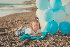 Baby cute girl with blond hair and pink apple cheek enjoying summer time holiday posing on sand beach sea side with blue white bal. Loons wearing casual kids Royalty Free Stock Image