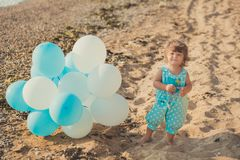 Baby cute girl with blond hair and pink apple cheek enjoying summer time holiday posing on sand beach sea side with blue white bal. Loons wearing casual kids Stock Image