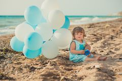 Baby cute girl with blond hair and pink apple cheek enjoying summer time holiday posing on sand beach sea side with blue white bal. Loons wearing casual kids Stock Photography