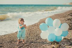 Baby cute girl with blond hair and pink apple cheek enjoying summer time holiday posing on sand beach sea side with blue white bal. Loons wearing casual kids Royalty Free Stock Photos