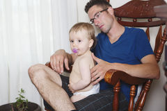 Baby with dad relax on the chair Royalty Free Stock Images