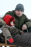 Baby and dad on sled. On a cold winter day. Winter fun Royalty Free Stock Photography