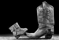 Baby and Daddy Cowboy. Baby Cowboy boot/Cowgirl and Daddy cowboy boot with room for your type in black and white royalty free stock photos