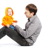 Baby on daddy's knees. Laughing baby sitting on daddy's knees Royalty Free Stock Photography