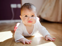 A baby with dark eyes in a white vest crawling on the floor Stock Photos