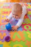 Baby, das auf Alphabetmatte erreicht Stockbild