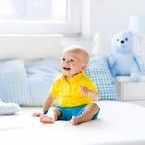 Baby, das auf Bett in der sonnigen Kindertagesstätte spielt Stockfotos