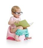 Baby, das auf Chamberpot mit Buch sitzt Lizenzfreie Stockfotografie