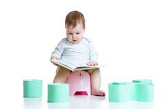 Baby, das auf Chamberpot mit Buch sitzt Stockfoto