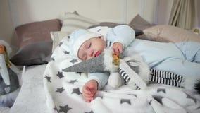 Baby, das auf dem Bett in den Schiebern und in der Kappe, netter Junge des süßen Traums, Kind umarmt ein Spielzeug beim Schlafen, stock video