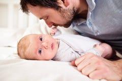 Baby, das auf dem Bett, gehalten von seinem Vater liegt Stockbild
