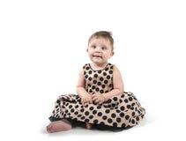 Baby, das auf dem Boden in einem schönen Kleid sitzt Lizenzfreies Stockfoto