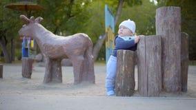 Baby, das auf dem Spielplatz im Park spielt Er steht nahe den Baumstümpfen Vor dem hintergrund eines hölzernen Rotwilds stock video