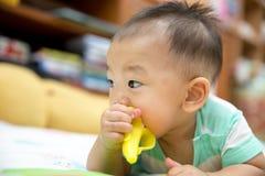 Baby, das auf Dentitionsplastikspielzeug kaut Stockbild