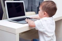 Baby, das auf der Computerhaustabelle spielt Lizenzfreies Stockfoto