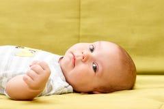 Baby, das auf der grünen Couch liegt Lizenzfreie Stockbilder
