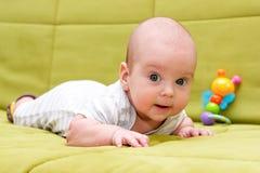 Baby, das auf der grünen Couch liegt Lizenzfreies Stockfoto