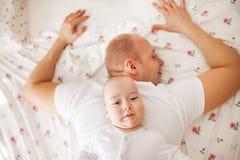 Baby, das auf der Rückseite seines Vaters sich entspannt stockbilder