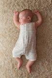 Baby, das auf einem Teppich schläft Lizenzfreie Stockbilder