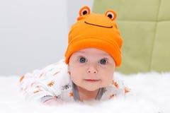 Baby, das auf einem weißen Pelz mit orange Kappe liegt Stockfotos