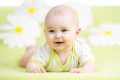 Baby, das auf grüner Wiese unter Gänseblümchen liegt Stockfoto