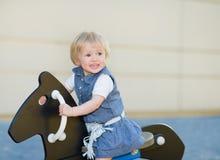 Baby, das auf Pferd auf Spielplatz schwingt Lizenzfreies Stockfoto