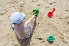 Baby, das auf Sand am Strand mit dem Spielzeuglöffelbagger, wässernd spielt Lizenzfreie Stockfotos