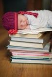 Baby, das auf Stapel Büchern schläft Stockbild