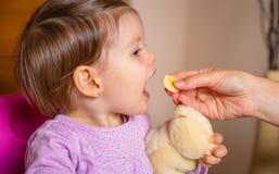 Baby, das Bananenscheibe von der Hand der Mutter isst Lizenzfreie Stockfotos