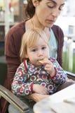 Baby, das Chips auf Mutterbeinen isst Lizenzfreies Stockfoto