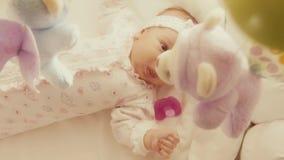 Baby, das defocused Spielzeugmobile in ihrem Feldbett betrachtet stock video